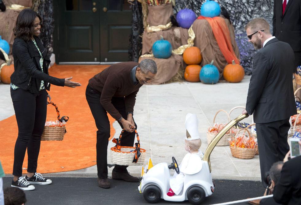 Los Obama repartiendo dulces a los niños qeu juegan al truco o trato en la Casa Blanca