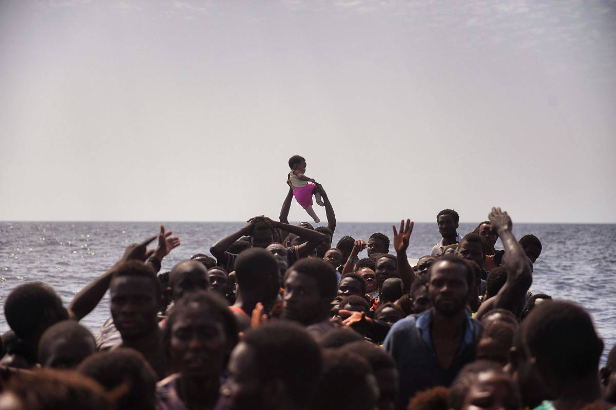 TOPSHOT - Migrants wait to be rescued by members of Proactiva Open Arms NGO in the Mediterranean Sea, some 12 nautical miles north of Libya, on October 4, 2016. At least 1,800 migrants were rescued off the Libyan coast, the Italian coastguard announced, adding that similar operations were underway around 15 other overloaded vessels. / AFP PHOTO / ARIS MESSINISARIS MESSINIS/AFP/Getty Images