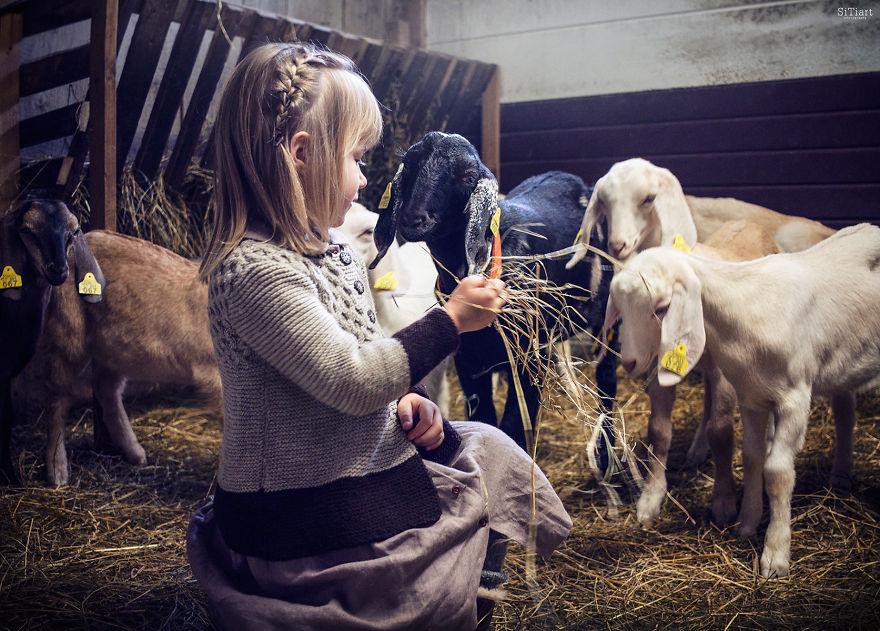 Fotografía de una niña alimentando a las cabras